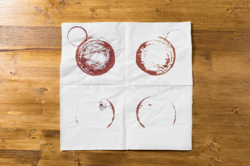 White napkin with wine trace on wooden background.  stock photo