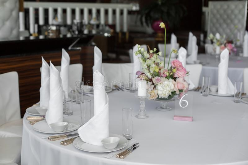 White napkins stand in white plates and bouquet of fresh flowers in the center of served table in the restaurant. clean white. Dishes layout on a white stock photo