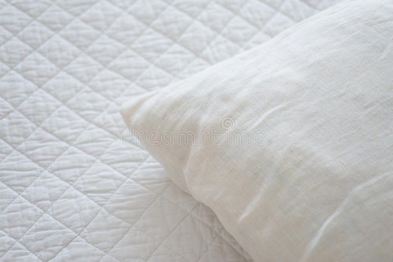 White natural textiles. Pillow lies on the bed cover made of natural textiles royalty free stock images