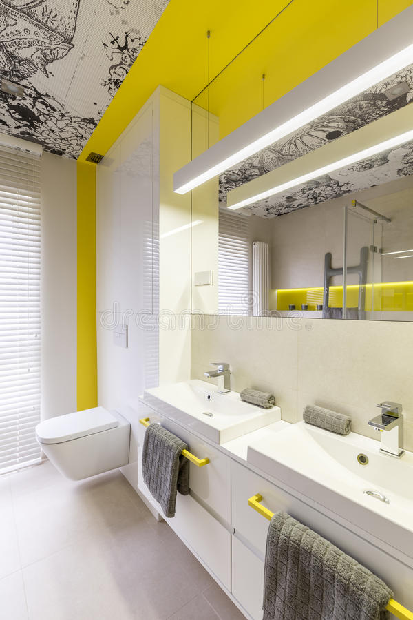 Neon yellow bathroom design idea. White and neon yellow bathroom design idea, yellow handles, double sink, toilet, graphic ceiling and window stock photography