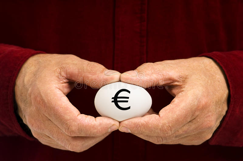 White nest egg with Euro symbol written on it. A man holds a white egg with the Euro symbol written on it, symbolizing the fragility of money matters and the royalty free stock photos