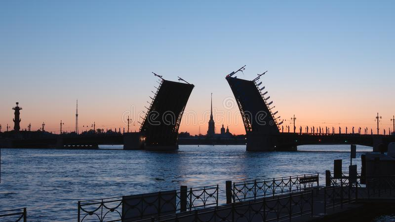 WHITE NIGHTS: Silhouette of opened Palace Bridge and Chapel of Peter and Paul Fortress background. St. Petersburg, Russia stock image