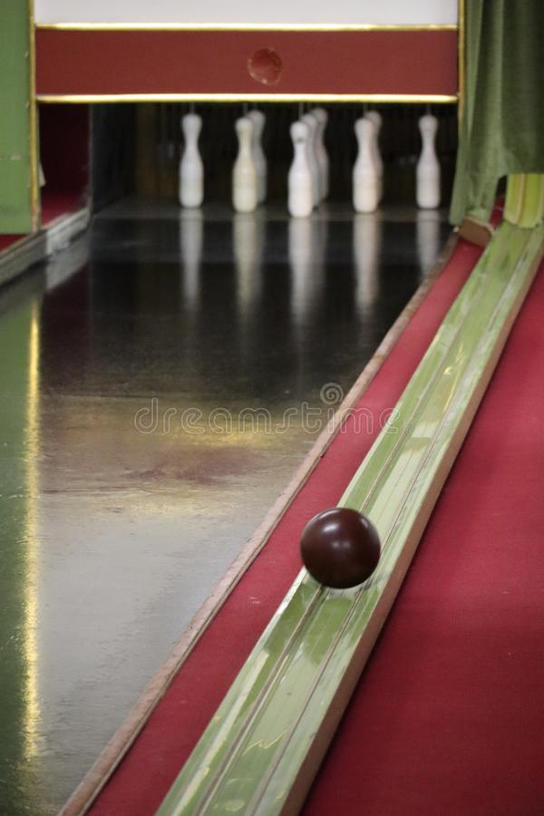 White ninepins on an old skittle alley and a brown ball rolling back royalty free stock photos