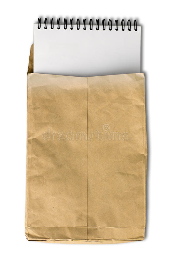 White note book in wrinkled brown paper envelope royalty free stock images