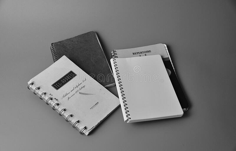 White Notebook on White and Black Book stock photography