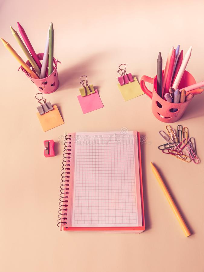 White notebook with original containers with colored pencils and school supplies. pink tone. Pink image with a white notebook and school material stock photos