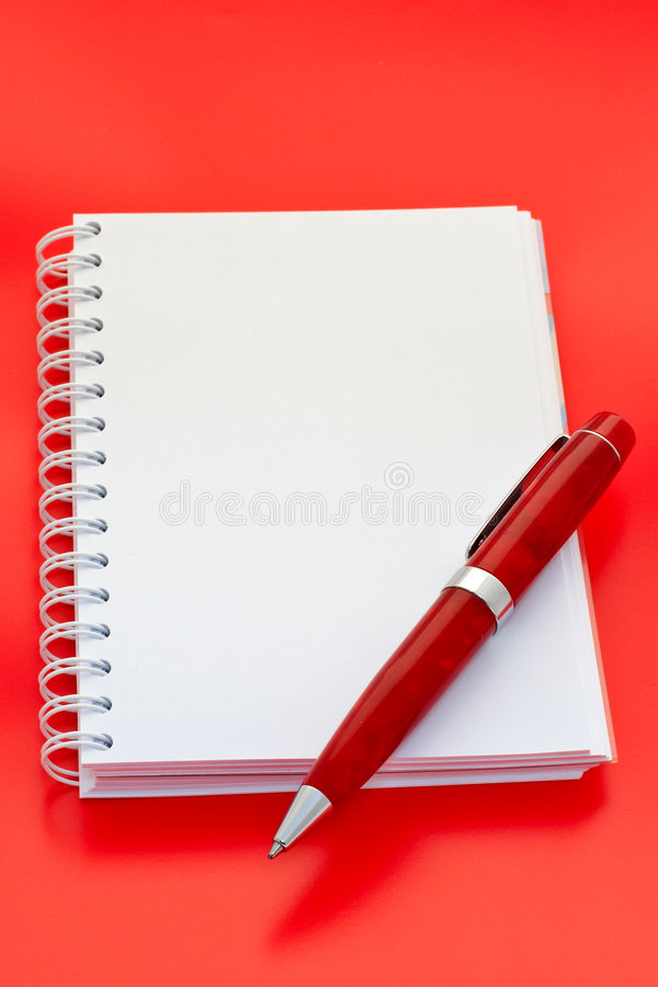 White notebook and pen. On red background stock image