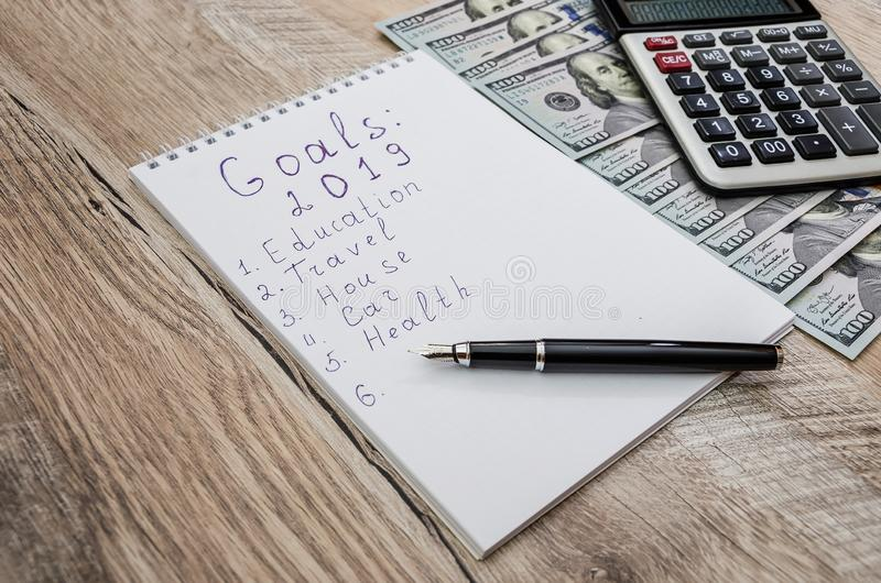 White notebook and pen, calculator and dollars close-up on wooden background stock image
