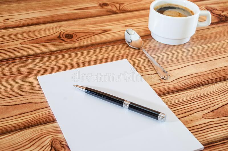 White notebook with pen and cup of coffee on wooden background. royalty free stock images