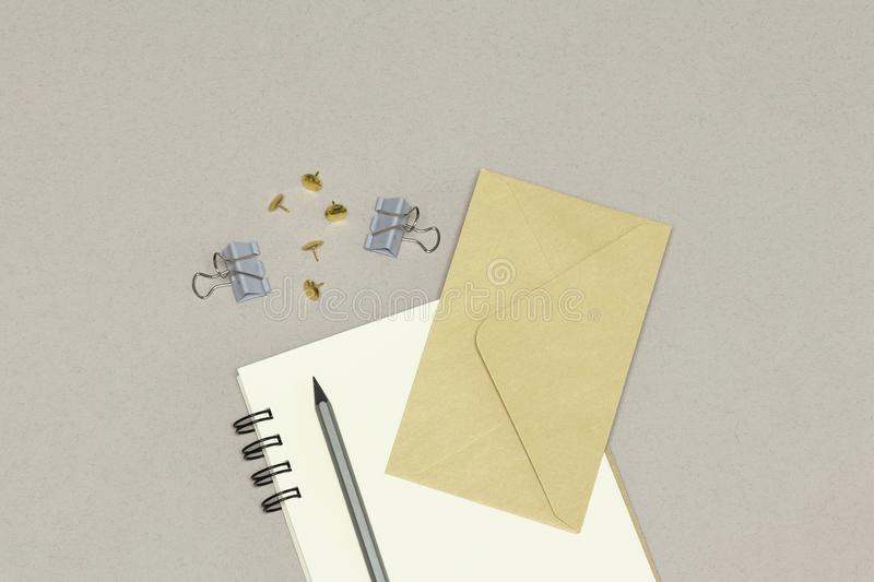 The notebook, envelope, silver pencil & paper clips on the grey background stock photography