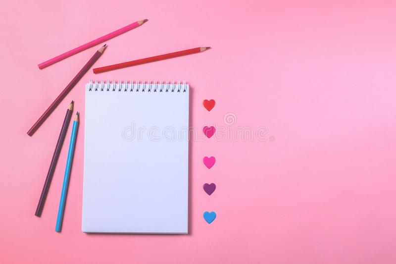White notebooks with colored pencils and pink background royalty free stock images