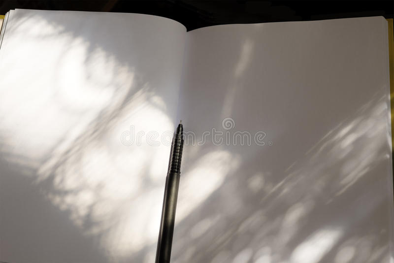 White notebook and black pen at the sunlight. White notepad and black pen set a contrast. Sunlight enhance the mood stock photo