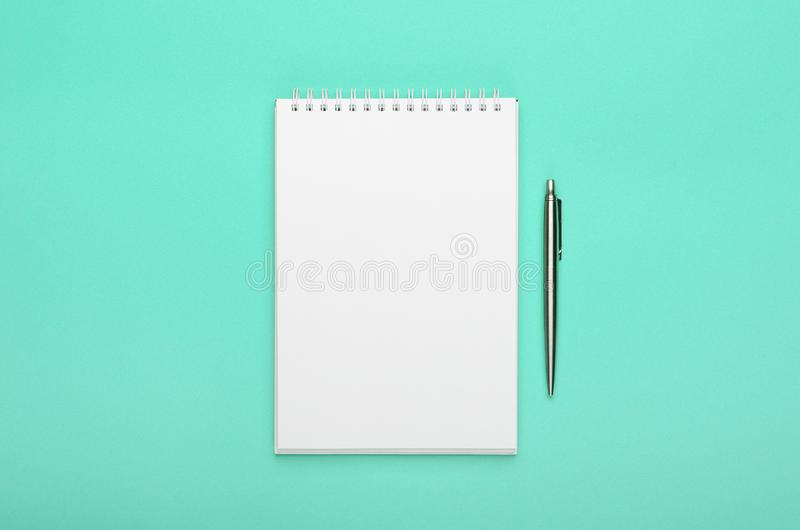 White notepad with steel pen on a turquoise background. Office table, minimal composition, copy space, mock up, template royalty free stock photography