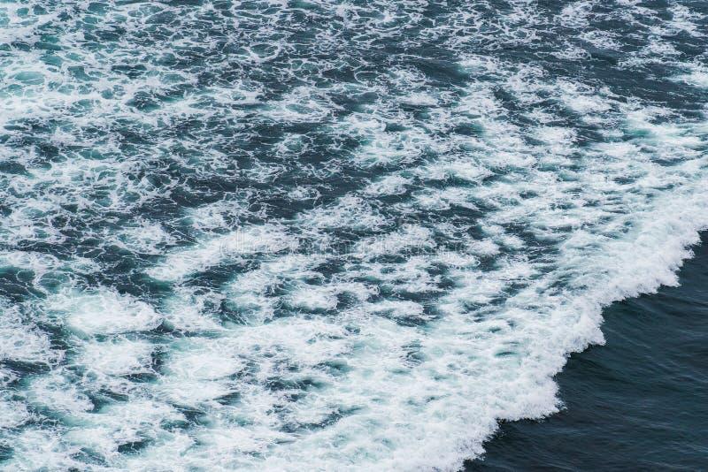 White ocean waves crashing over coastal sea rocks in summer. royalty free stock photo