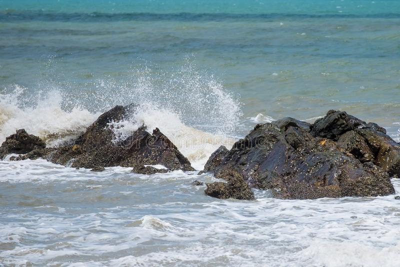 White ocean waves crashing over coastal sea rocks in summer.Thailand. White ocean waves crashing over coastal sea rocks in summer.Thailand royalty free stock images