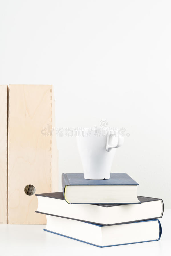 White office desk with books, cup and folders. Copy space - study or workplace background mock up royalty free stock image