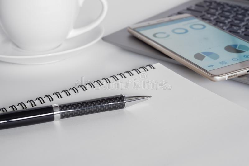 White office desk with laptop, coffee, mobile phone with business analysis graph, notebook with pen with copy space for your text royalty free stock image