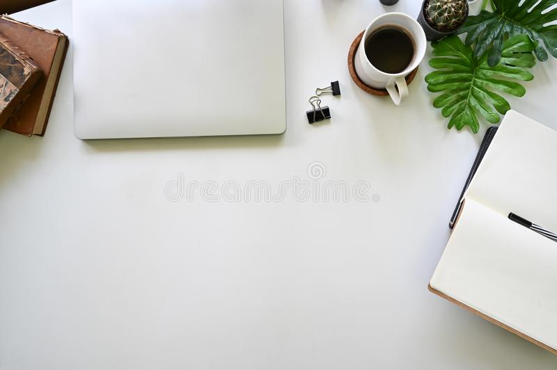 White office desk laptop, notebook and pen with cactus on top view table royalty free stock images