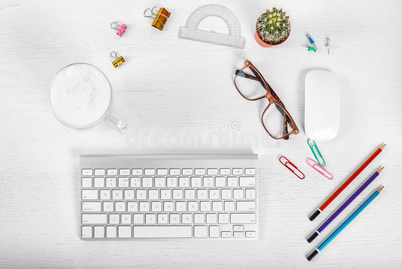 White office desk table with computer mouse and keyboard, cup of latte coffee, pencils and eye glasses. Top view with copy space, stock photo