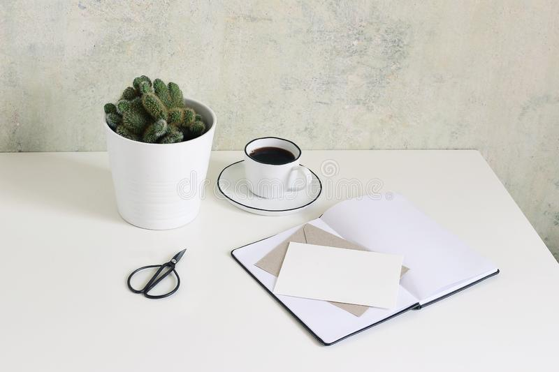 White office desk table mock-up scene with cup of coffee, cactus, open notebook, blank greeting card, envelope and stock photography