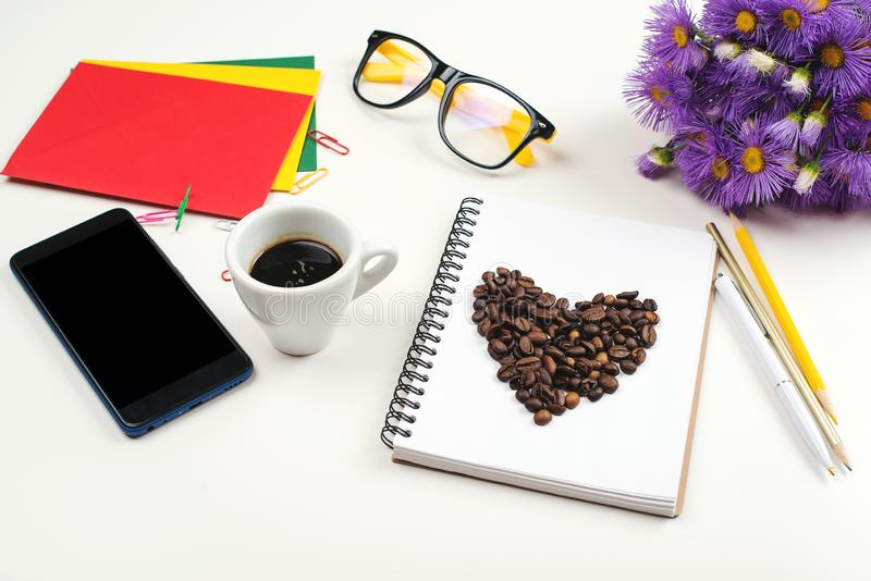 White office desk table with notebook, pen, glasses, cup of fresh espresso coffee. Spring flowers and mobile phone at table. royalty free stock photo