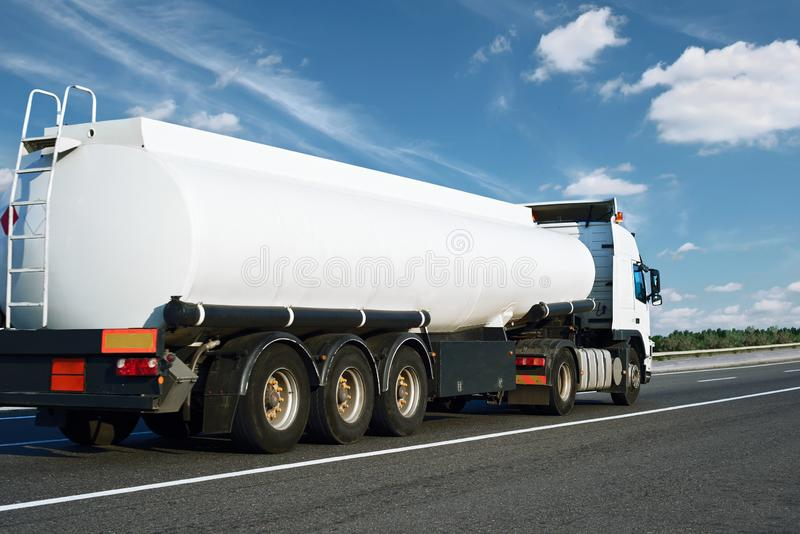 The white oil truck is going up the road. Cargo transportation concept royalty free stock photos