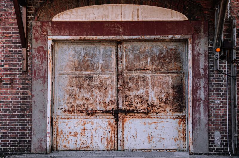 White old rusty iron gate with red brick wall loft warehouse. White old rusty iron gate with red brick wall industrial loft retro vintage warehouse wall royalty free stock photos