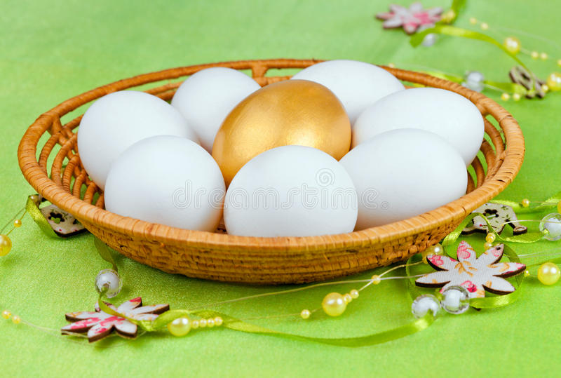 White and one golden eggs stock photos