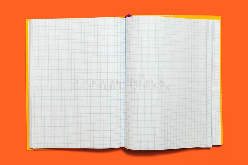 Opened workbook on an orange background. White opened workbook lying on an orange background. concept of business or educational equipment. free copyspae royalty free stock images