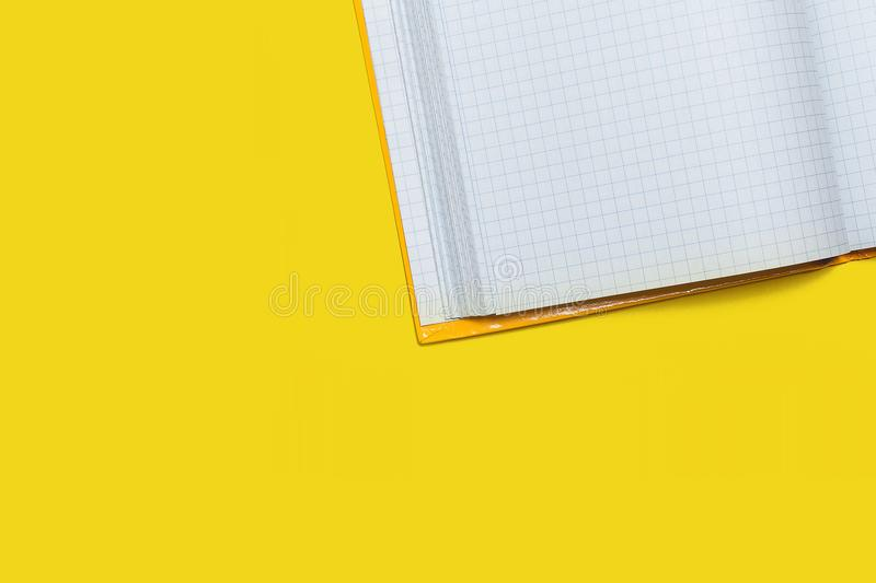 Opened workbook on a yellow background. White opened workbook lying on a yellow background. concept of business or educational equipment. free space for royalty free stock photography