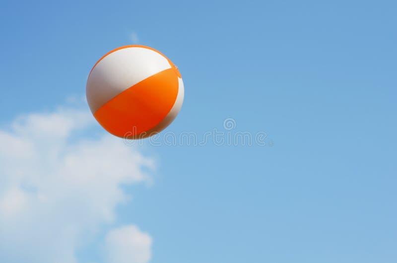 Beach ball flying on blue sky royalty free stock photos