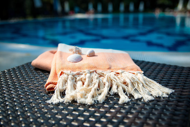 A white and orange Turkish peshtemal / towel and white seashells on rattan lounger with blue a swimming pool as background. stock images