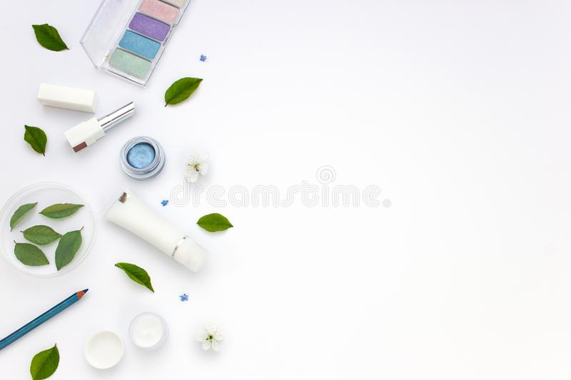 White cosmetics flat lay frame with flowers and leaves. Clean beauty concept royalty free stock photos