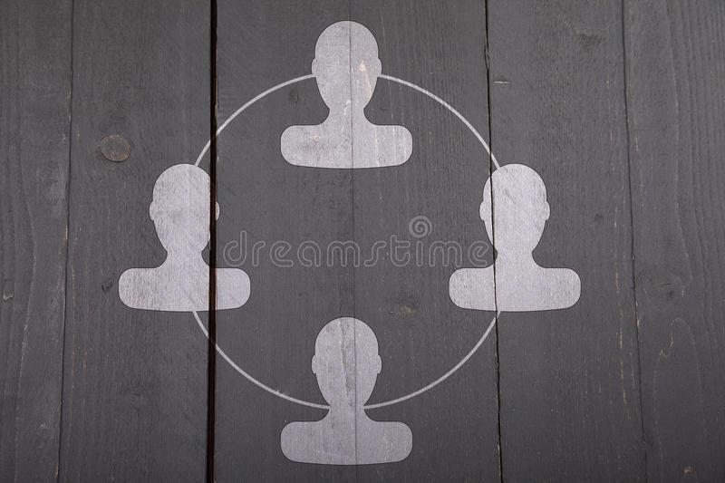 White organigram with white heads on black wooden background. White organigram with white heads on dark black wooden background stock image