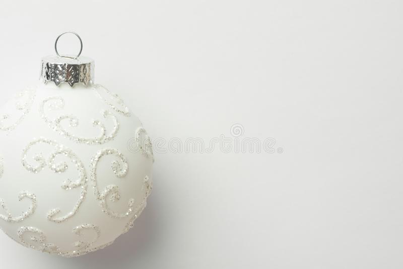 White ornament Christmas tree ball on same color monochrome background. New Year greeting card poster in Scandinavian style. White ornament Christmas tree ball royalty free stock images
