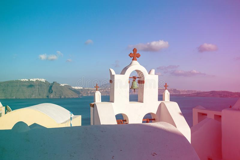 White orthodox church bell tower with ocean and rest of the island on the background. Oia, Santorini. colored light leak stock image