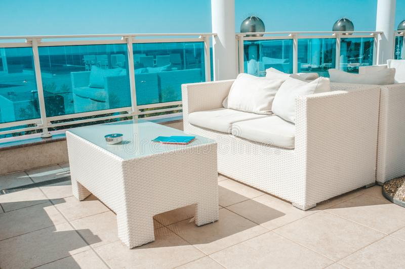 White outdoor furniture soft sofas and rattan chairs with cushions and a table with a glass top. Place to relax on the terrace of. The resort royalty free stock image