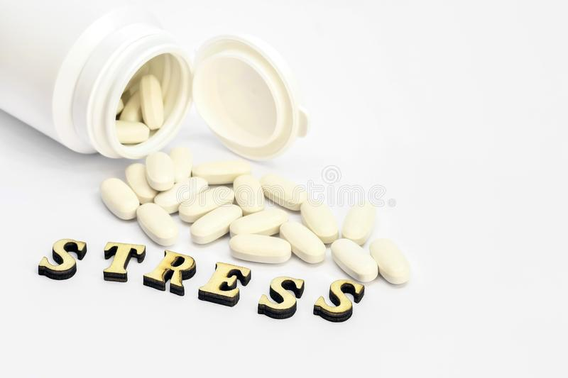 White oval pills spilled out of a white bottle on a white background labeled stress close-up royalty free stock photography