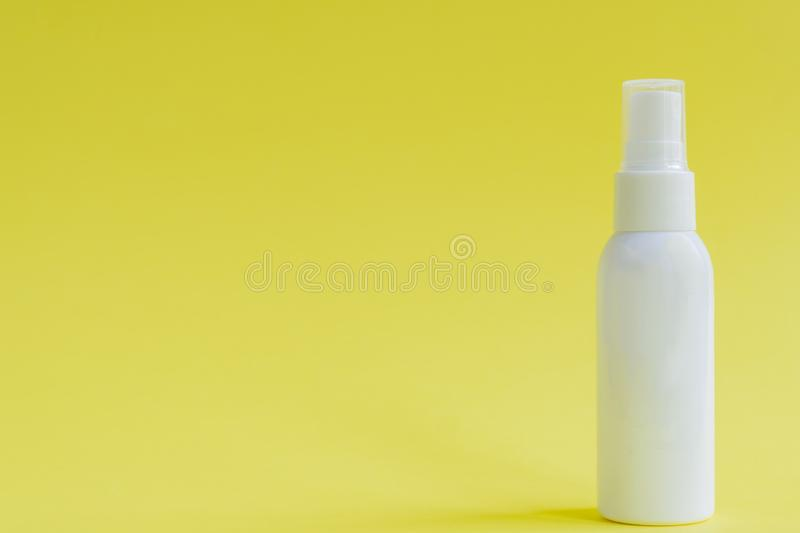 White packaging spray cosmetic plastic bottle on yellow background. Mockup for hair or body care products.  royalty free stock image