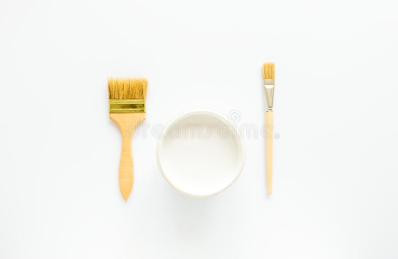 White paint and brushes for house repairing and painting on white background. Flat lay. White paint and brushes for house repairing and painting on white royalty free stock photos