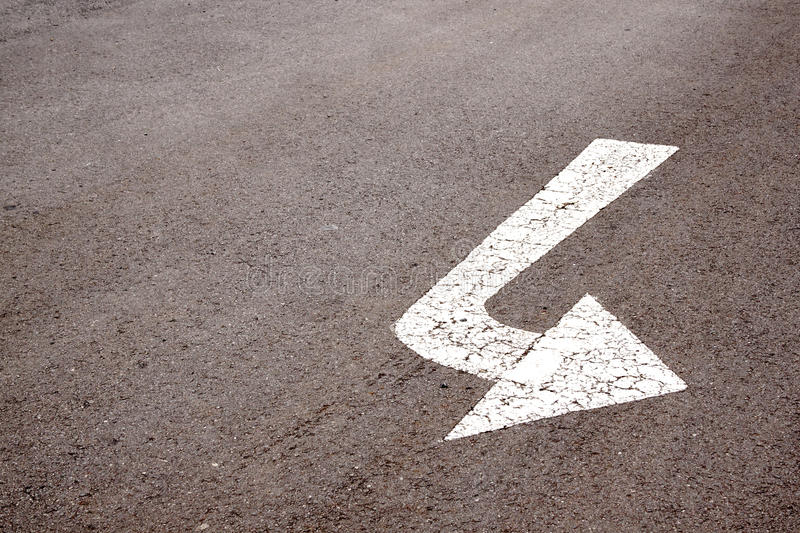 White Painted Arrow Indicating Left Turn On Road Surface royalty free stock image
