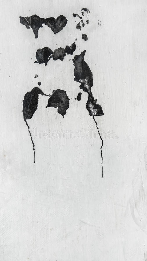 White painted metal wall with abstract spots of black paint. The vertical frame stock photo