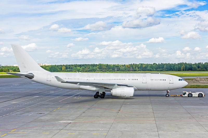 White painted passenger jet airplane pushed back from the parking stock photos
