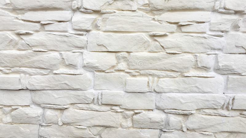 White painted stone wall texture as background. Cracked concrete vintage block stone wall background, old painted wall. Background royalty free stock image