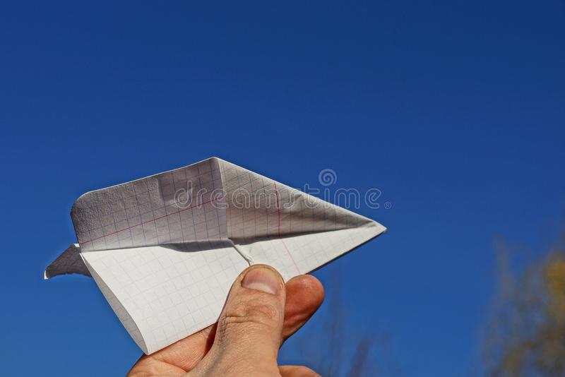 White paper airplane in hand on blue sky background stock photography