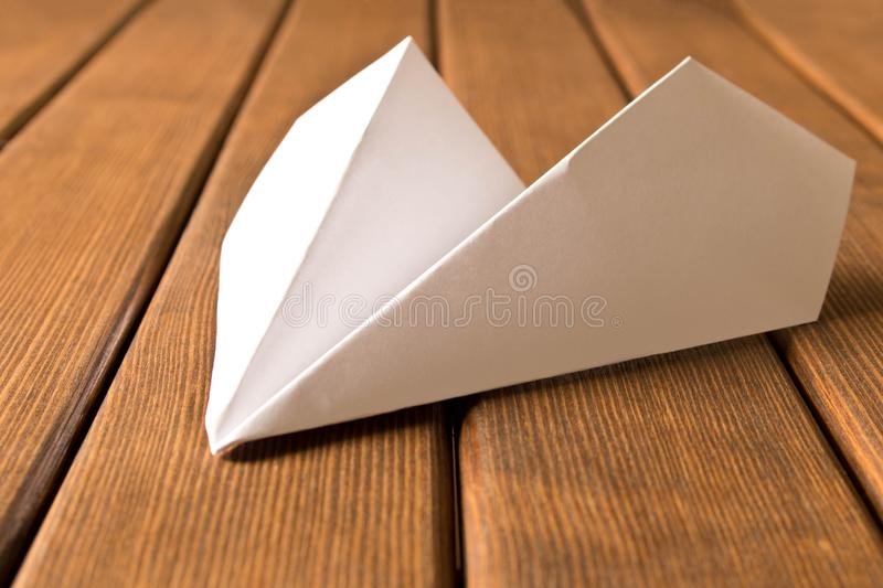 White paper airplane on wooden background. Travel concept royalty free stock photography