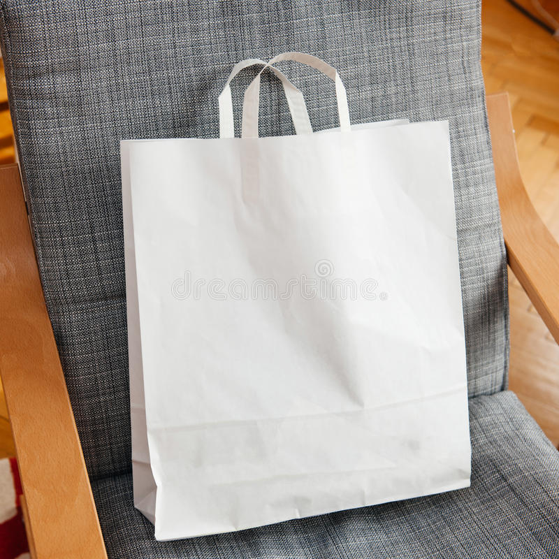 White paper bag on armchair. White fashion bag with logo copy space on armchair stock photo