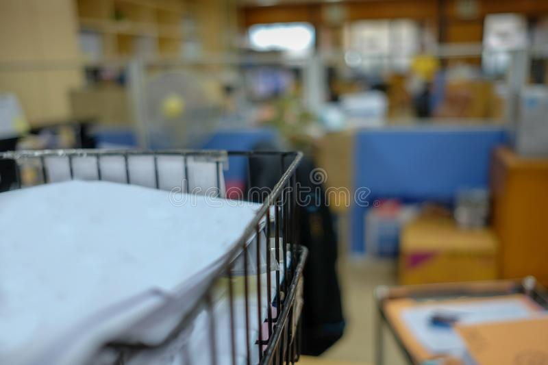 White paper on Black basket have bluring office background. Stack, papers, pile, business, documents, desk, work, paperwork, unfinished, information royalty free stock photography
