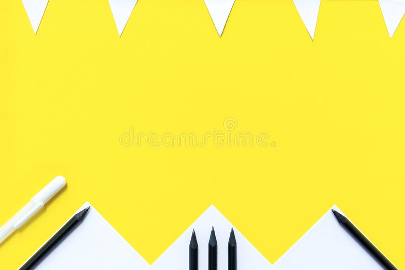 White paper, black pencils, white pens, and a garland of flags are randomly arranged on a yellow background. The concept is back to school. White paper, black stock photography
