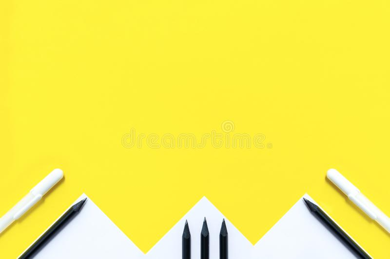 White paper, black pencils and white pens are randomly arranged on a yellow background. The concept is back to school. White paper, black pencils and white pens royalty free stock photos
